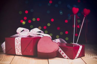 Gifts in red boxes for Valentine's day. Red heart on a wooden table against the background of colorful bokeh.